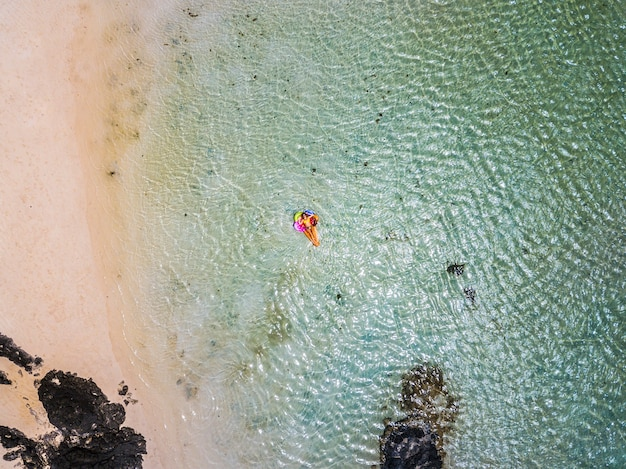 Vue aérienne de personnes en vacances d'été avec une belle fille sur un lilo tendance coloré se détendre et bronzer sur l'eau de plage du lagon océan vert clair