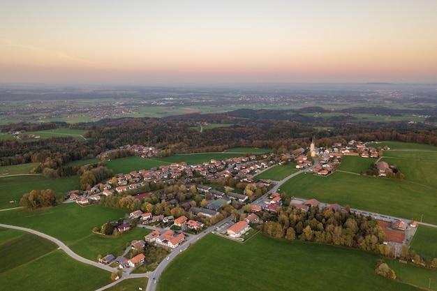 Vue aérienne de la petite ville aux toits de tuiles rouges parmi les champs agricoles verts