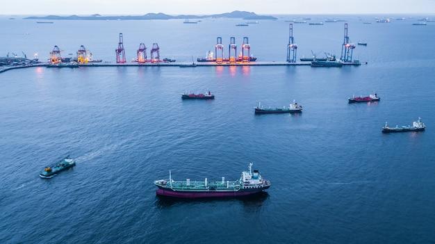 Vue aérienne d'un pétrolier et d'un camion-citerne de gaz chargés dans un port en mer la nuit.