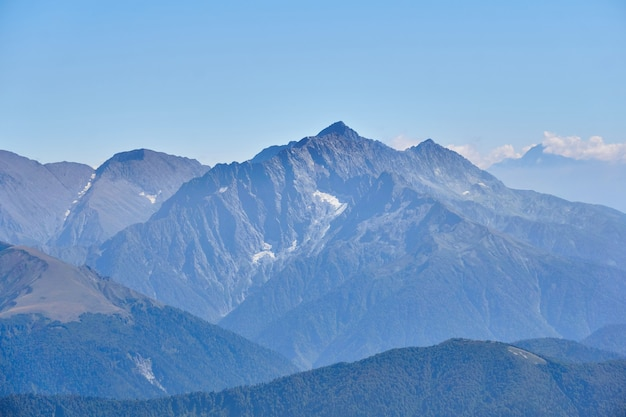 Vue aérienne des pics montagneux pointus avec des glaciers dans la brume atmosphérique bleue
