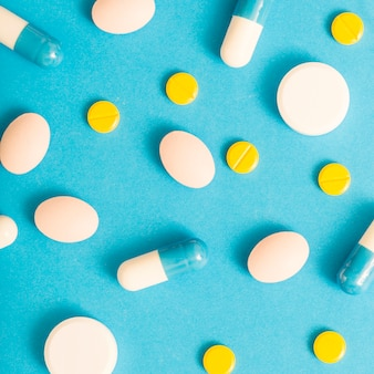 Vue aérienne de pilules blanches, jaunes et capsules sur fond bleu