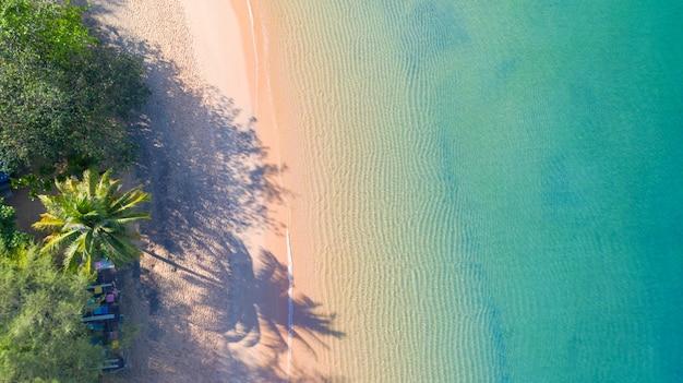 Vue aérienne de la plage avec de l'eau bleue émeraude et de la mousse à vagues sur la mer tropicale