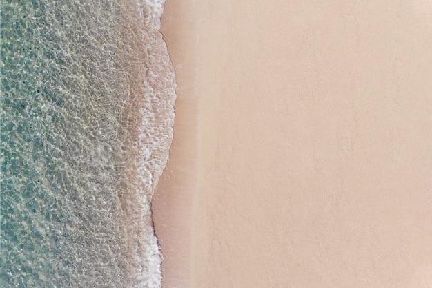 Vue aérienne de la plage de sable et de la mer bleue avec la vague