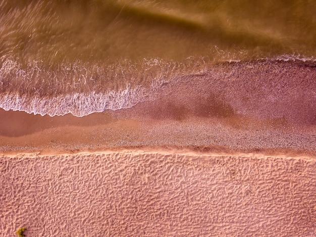 Vue aérienne de la plage de sable et de la mer avec des vagues