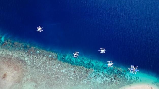 Vue aérienne de la plage de sable avec les touristes en train de nager dans une belle eau de mer claire de l'île de sumilon atterissant près d'oslob, cebu, aux philippines. - accélérer le traitement des couleurs.