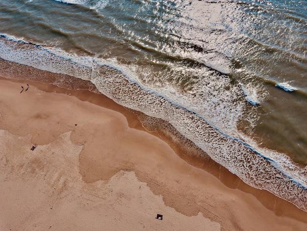 Vue aérienne de la plage de sable et vue de dessus des vagues de la mer