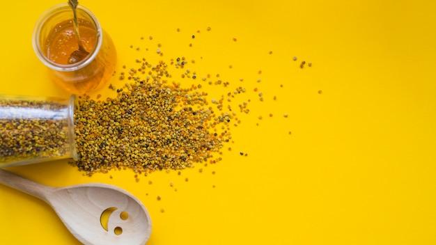 Une vue aérienne des pollens d'abeilles déversés; pot de miel et smiley cuillère de bois sur fond jaune