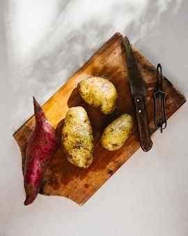 Vue aérienne de pommes de terre crues sur une planche à découper en bois