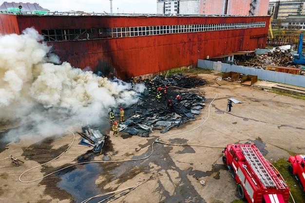 Vue aérienne des pompiers éteignant l'incendie dans la zone industrielle.