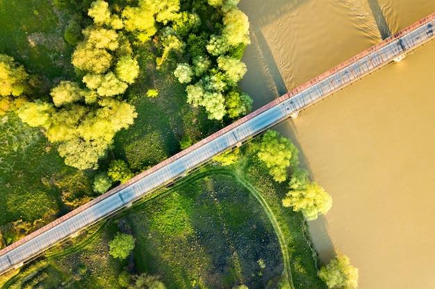 Vue aérienne d'un pont routier étroit qui s'étend sur une large rivière boueuse dans une zone rurale verte.
