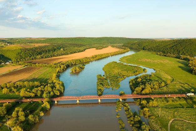 Vue aérienne d'un pont routier étroit s'étendant sur une large rivière boueuse dans une zone rurale verte.