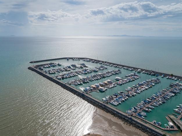Vue aérienne sur le port avec des yachts de luxe - port de voiliers, nombreux voiliers à voiles amarrés dans le port avec des nuages de ciel bleu.
