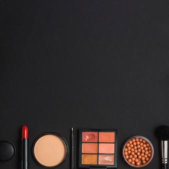Vue aérienne des produits de maquillage au fond du fond noir