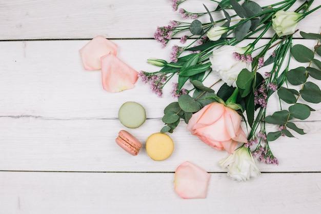 Une vue aérienne de rose; bouquet de fleurs de limonium et d'eustoma avec des macarons sur un bureau en bois blanc