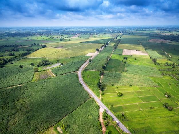Vue aérienne d'une route de campagne au milieu de champs avec une voiture blanche