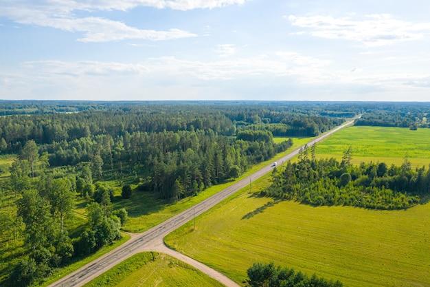 Vue aérienne sur route de campagne rurale à travers la forêt, les terres agricoles et les villages de lettonie