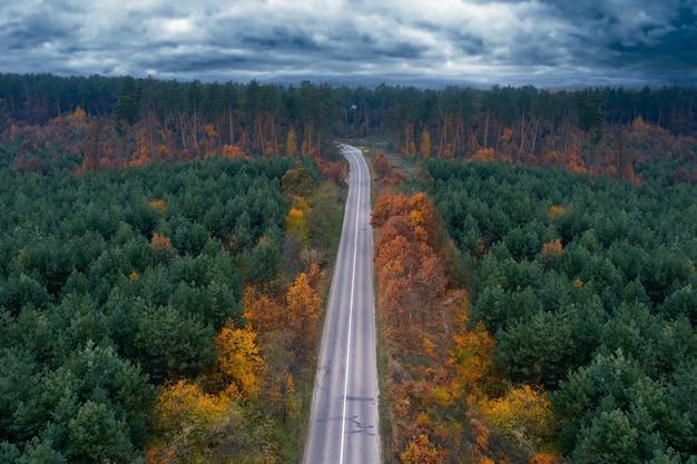 Vue aérienne de la route de campagne vide dans la forêt d'automne en journée nuageuse.