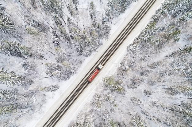 Vue aérienne de la route couverte de neige dans la forêt d'hiver avec un camion passant par