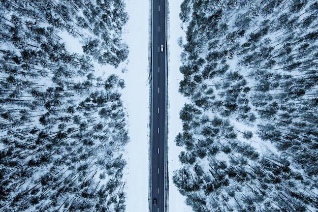 Vue aérienne d'une route dans une forêt couverte de neige en hiver
