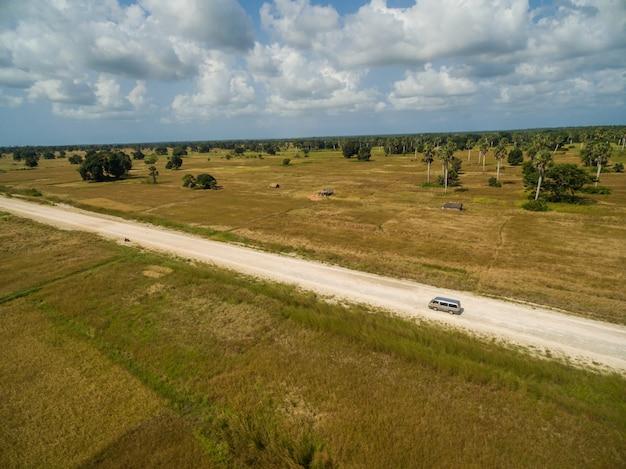 Vue aérienne d'une route entourée de champs couverts d'herbe capturés à zanzibar, afrique