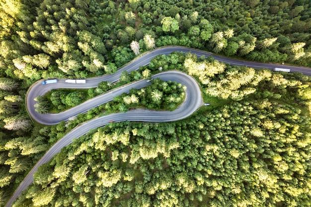 Vue aérienne de la route sinueuse dans le col de haute montagne à travers des forêts de pins verts denses.