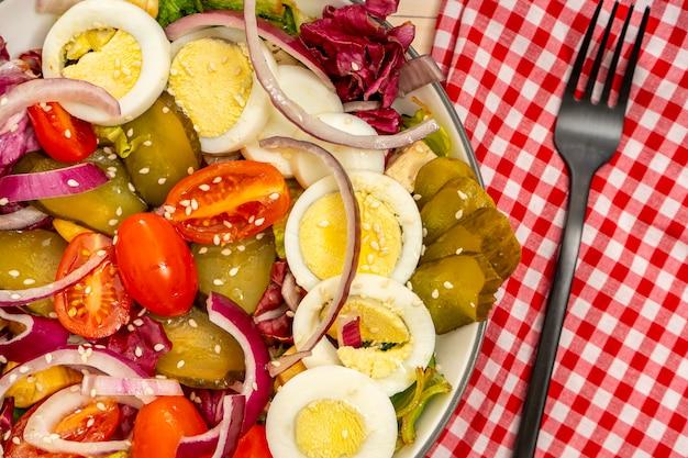 Vue aérienne d'une salade saine et nutritive de laitue, tomate cerise, œuf, concombre et oignon rouge aux graines de sésame. orientation horizontale, vue partielle