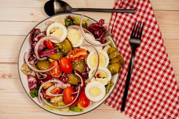 Vue aérienne d'une salade saine et nutritive de laitue, tomate cerise, œuf, concombre et oignon rouge aux graines de sésame. orientation horizontale