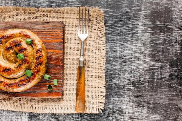 Vue aérienne de saucisse en spirale grillée avec échalote sur une planche à découper sur fond texturé en bois
