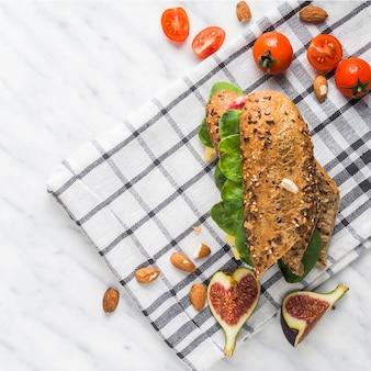 Vue aérienne d'un savoureux hot-dog; amandes; tranches de figues fraîches et tomates cerises sur la serviette sur fond blanc