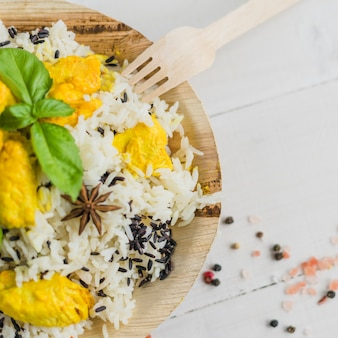 Vue aérienne de savoureux poulet et riz en assiette avec des feuilles de basilic
