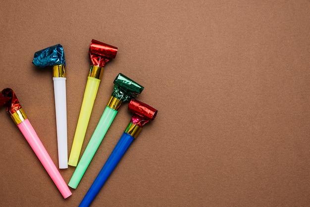 Une vue aérienne de souffleurs de corne de fête colorée sur fond marron