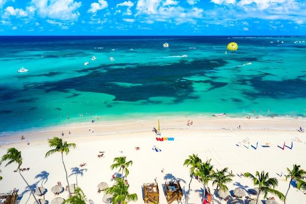 Vue aérienne de la station balnéaire de bavaro beach punta cana en république dominicaine. belle plage tropicale atlantique avec palmiers, parasols et ballon de parachute ascensionnel.