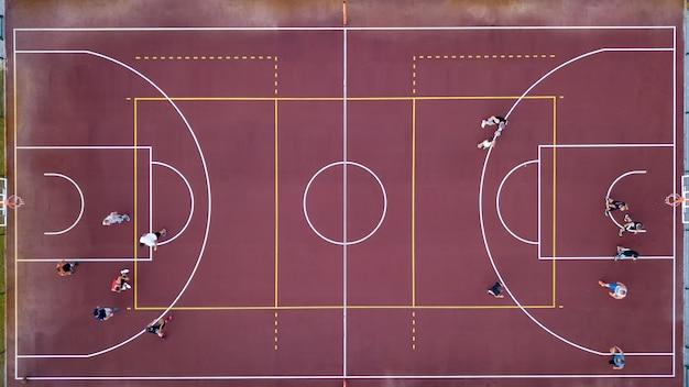 Vue aérienne strictement d'en haut avec le drone jusqu'à un terrain de basket avec joueurs et ballon. jeu de sport en basketball. vue de dessus.