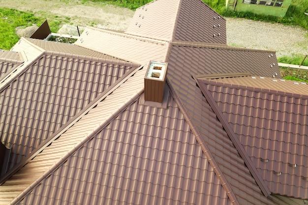 Vue aérienne de la structure du toit de la maison recouverte de feuilles de tuiles métalliques brunes.