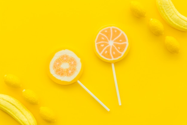 Vue aérienne des sucettes aux agrumes; bonbons à la banane et au citron sur la surface jaune