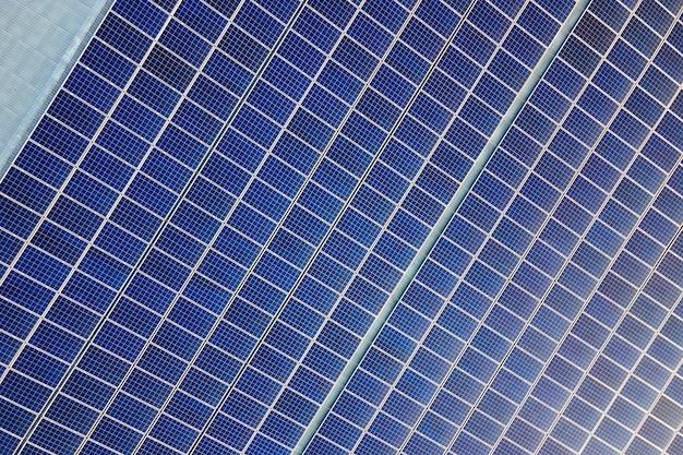 Vue aérienne de la surface des panneaux solaires photovoltaïques bleus montés sur le toit du bâtiment pour produire de l'électricité écologique propre. production de concept d'énergie renouvelable.