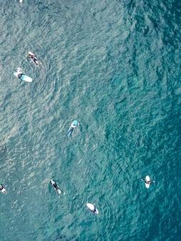 Vue aérienne des surfeurs dans les eaux azurées du fond de l'océan atlantique