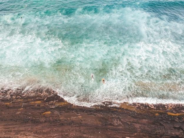 Vue aérienne des surfeurs dans les vagues de l'océan atlantique. fond de plage de sable