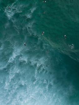 Vue aérienne de surfeurs nageant allongés sur leurs planches dans la mer en attendant de fortes vagues à venir