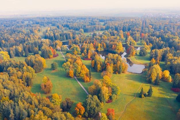 Vue aérienne survolant le parc de la vallée d'automne avec des prairies et une rivière sinueuse, des étangs, des arbres lumineux.