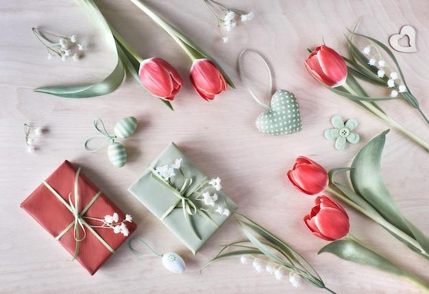 Vue aérienne de la table en bois clair avec des décorations de printemps, des cadeaux emballés, des fleurs blanches, des tulipes rouges et des oeufs de pâques