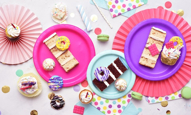 Une vue aérienne de la table décorée de couleurs vives avec de délicieux morceaux de gâteau