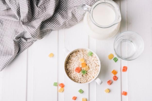 Vue aérienne d'une table avec pichet à lait, verre et bol d'avoine avec des bonbons à la gelée