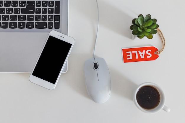 Vue aérienne de téléphone portable sur ordinateur portable avec étiquette de vente et de café sur la table blanche