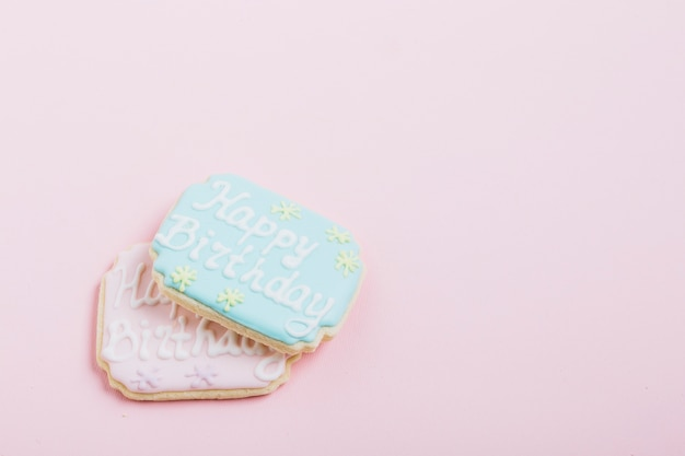 Vue aérienne de texte joyeux anniversaire sur des biscuits frais sur fond rose