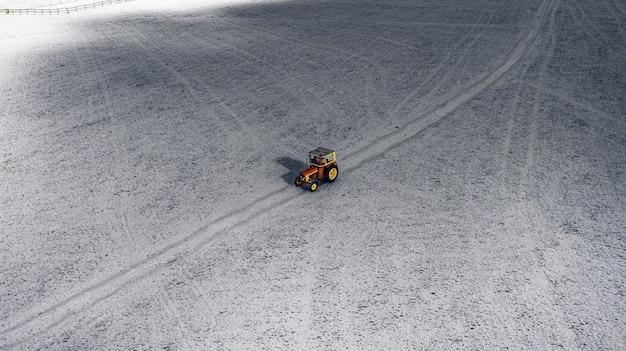 Vue aérienne d'un tracteur sur un champ enneigé