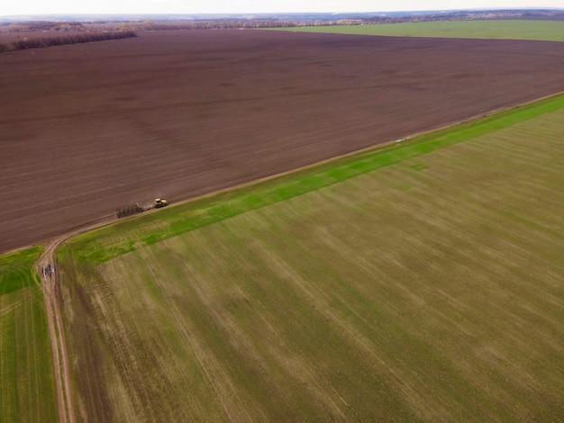 Vue aérienne d'un tracteur jaune moderne traverse le champ, labourant le champ agricole sec
