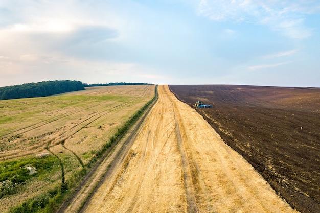 Vue aérienne d'un tracteur labourant le champ agricole de l'agriculture noire après la récolte à la fin de l'automne.