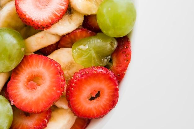 Une vue aérienne de tranches de fraises et bananes avec des raisins sur fond blanc