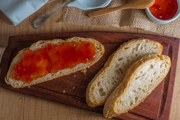 Vue aérienne de tranches de pain maison, certaines enduites de confiture. fond rustique.